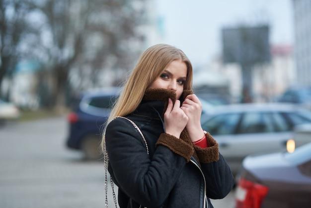 Caffè bevente della giovane bella donna e camminare intorno alla città