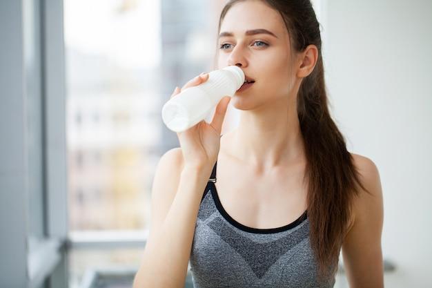 Giovane bella donna che beve dalla bottiglia di plastica di yogurt.