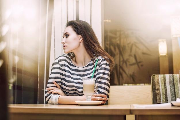 Giovane bella donna che beve latte nella caffetteria a un tavolo vicino alla finestra sotto il bagliore delle luci