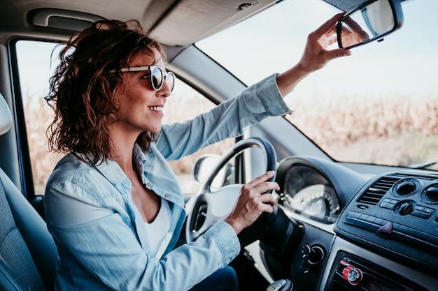 Giovane bella donna che guida un'auto e che regola lo specchietto retrovisore. concetto di viaggio