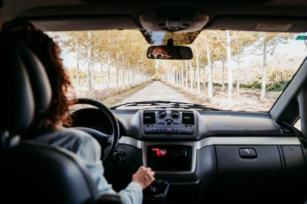 Giovane bella donna che guida un furgone da un percorso di alberi. concetto di viaggio, vista dall'interno