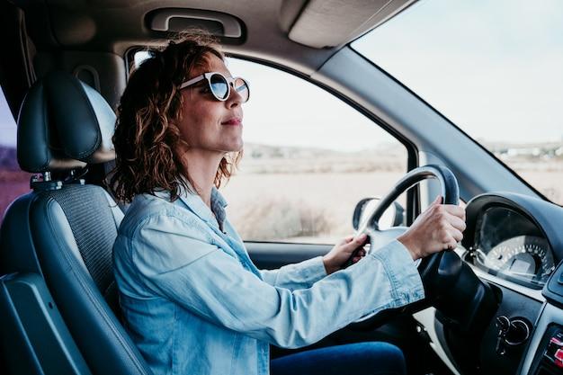 Giovane bella donna alla guida di un furgone. concetto di viaggio