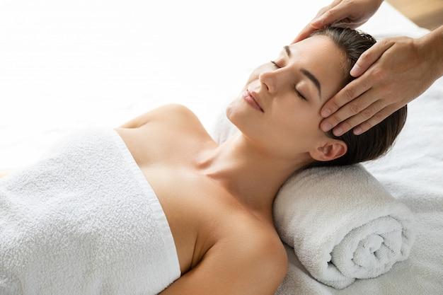 Giovane e bella donna durante la sessione di massaggio facciale