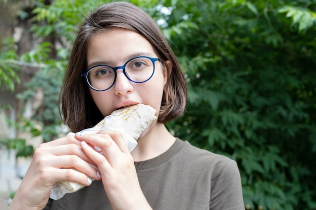 Giovane bella donna che mangia fast food mentre si cammina nel parco