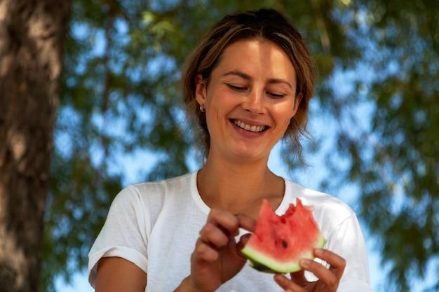 Una giovane bella donna mangia un grosso pezzo di anguria durante un picnic in una calda giornata estiva, sullo sfondo un grande albero verde