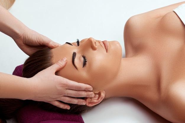Giovane bella donna che gode del massaggio facciale antietà
