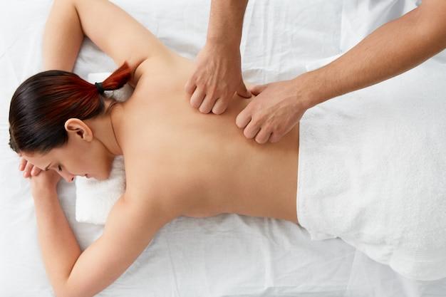Giovane bella donna che gode di un massaggio alla schiena.