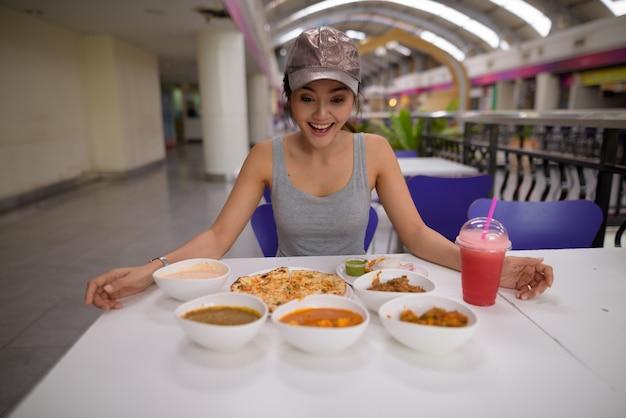 Giovane bella donna che gode del cibo indiano al ristorante