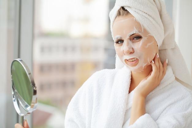 Giovane bella donna in una maschera per il viso, cura della pelle. Foto Premium