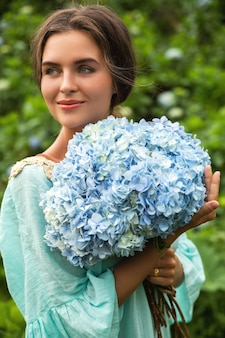 Fiorista di giovane e bella donna che raccoglie fiori di ortensie nel campo
