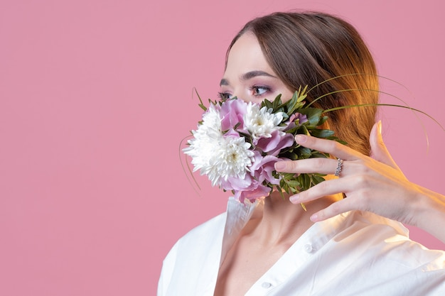 Giovane bella donna con una maschera per il viso a fiori