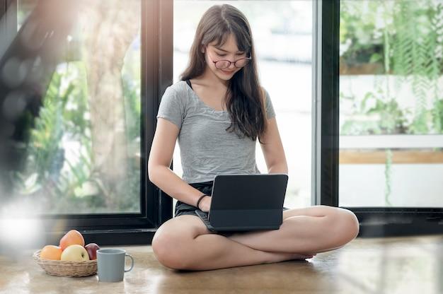 Giovane bella donna con gli occhiali che lavora al computer portatile durante il soggiorno a casa, il lavoro a distanza, l'apprendimento online del concetto.