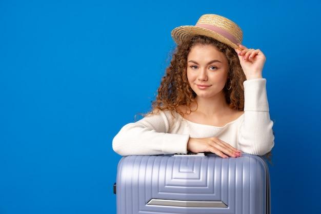 Giovane bella donna in cappello in vacanza con la valigia su sfondo blu