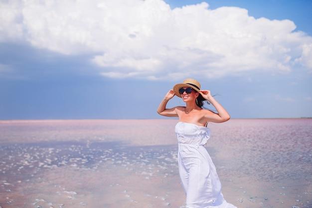Giovane bella donna che ha divertimento sulla spiaggia tropicale