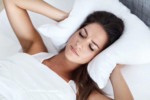 Giovane bella donna che ha problemi a dormire