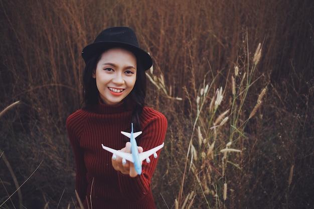 La giovane bella donna tiene l'aereo con emozione felice al bellissimo campo in erba.