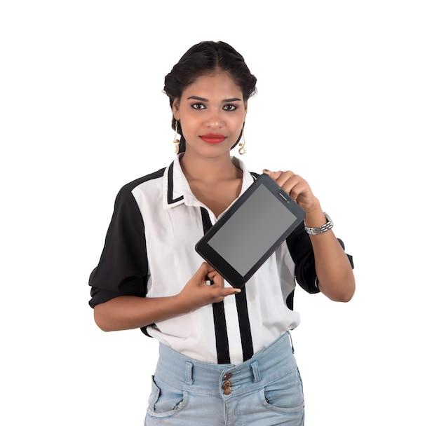 Giovane bella donna che tiene telefono astuto dello schermo in bianco sulla parete bianca