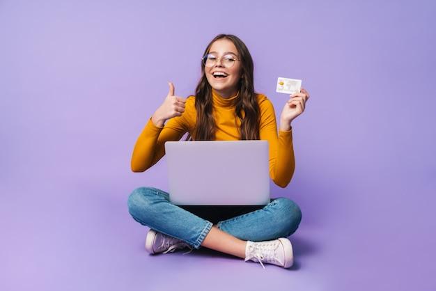 Giovane bella donna che tiene la carta di credito e usa il computer portatile mentre è seduta con le gambe incrociate isolate