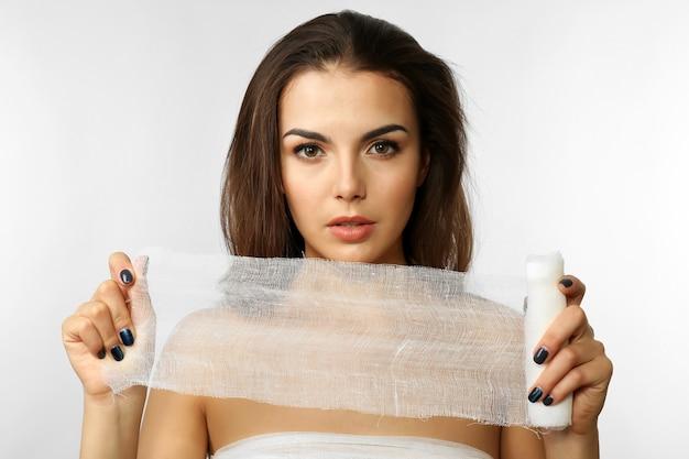 Giovane bella donna, tenendo una garza, isolata su bianco, primo piano