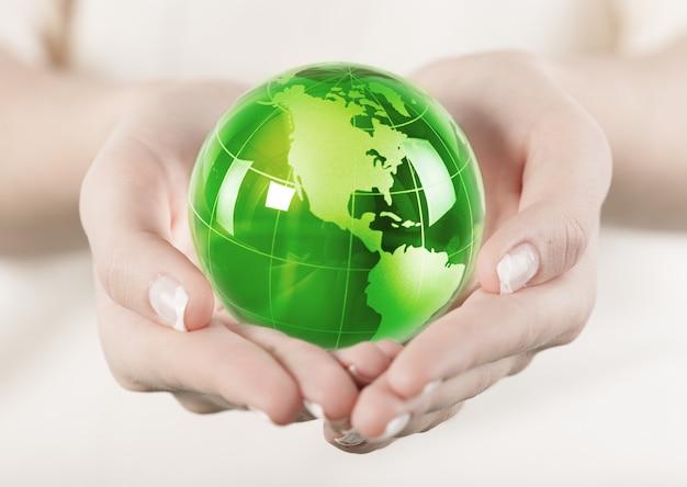 Giovane bella donna che tiene il globo verde nelle mani