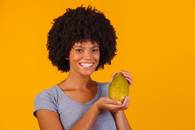 Giovane bella donna che tiene papaia su giallo