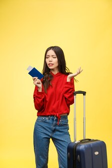 Passaporto della tenuta della giovane bella donna che sembra sorpreso