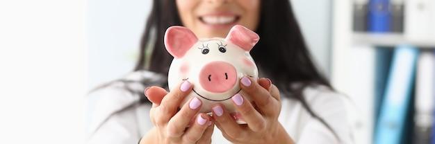 Giovane bella donna che tiene banca piggy a forma di maiale nelle mani