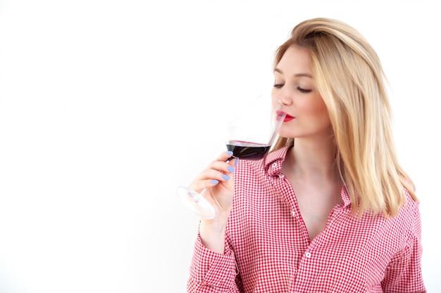 Giovane bella donna che tiene il bicchiere di vino rosso su bianco