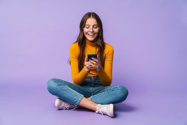 Giovane bella donna che tiene lo smartphone mentre è seduto con le gambe incrociate isolato