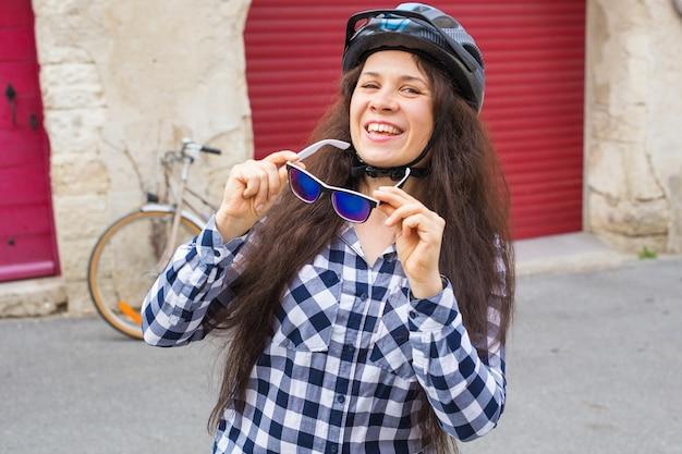 Giovane bella donna che tiene gli occhiali da sole sulla bicicletta di sfondo e sulla porta rossa