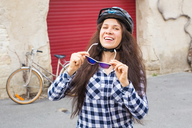 Giovane bella donna che tiene gli occhiali da sole sulla bicicletta da parete e sulla porta rossa.