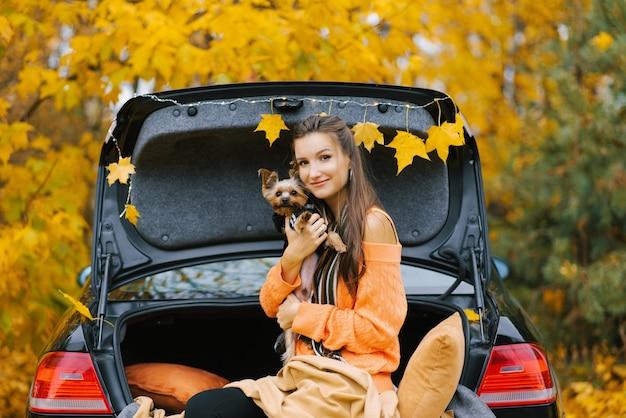 Una giovane bella donna tiene il suo amato animale domestico all'aria aperta contro un bosco in autunno. concetto di viaggio