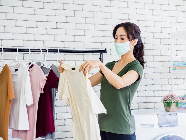 Giovane bella donna, casalinga che indossa un panno casual e una maschera protettiva che tiene la camicia, controllando la macchia sporca su di essa dopo il lavaggio prima dell'asciugatura sul muro bianco del bucato.