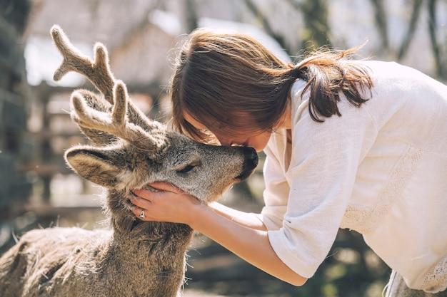 Giovane bella donna che abbraccia cervo capriolo animale sotto il sole, proteggendo un animale