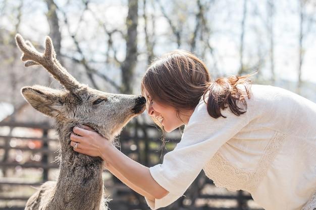 Giovane bella donna che abbraccia cervo capriolo animale sotto il sole