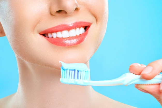 La giovane bella donna è impegnata nella pulizia dei denti. denti bianchi sani di bel sorriso. una ragazza tiene uno spazzolino da denti. il concetto di igiene orale. immagine promozionale per una stomatologia, clinica dentale.