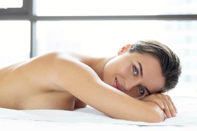 Giovane e bella donna sta mentendo e rilassarsi dopo il massaggio
