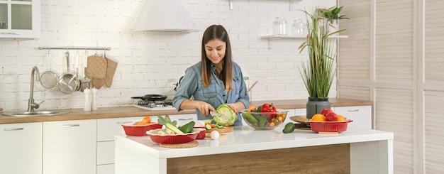 Una giovane bella donna sta preparando un'insalata di varie verdure in cucina. il concetto di una dieta e uno stile di vita sani.