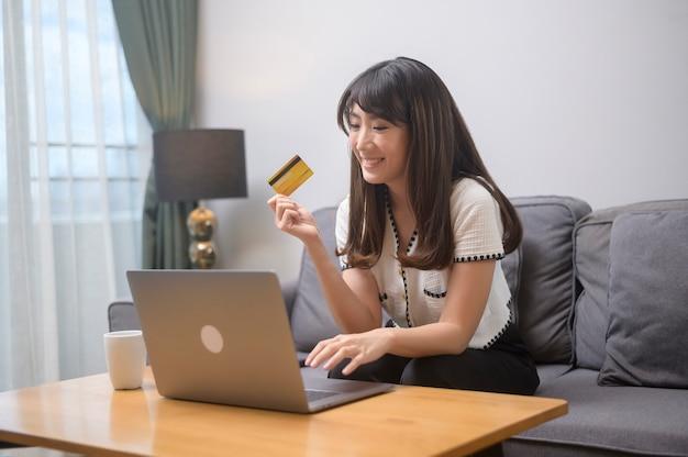 Una giovane bella donna sta usando la carta di credito per lo shopping online sul sito internet a casa, concetto di e-commerce