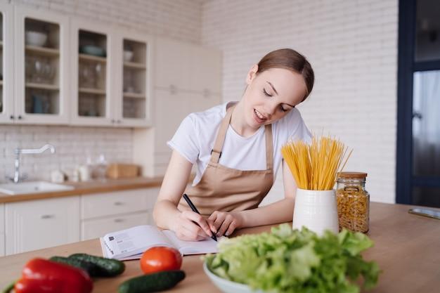 La giovane bella donna in cucina in un grembiule scrive le sue ricette preferite accanto alle verdure fresche