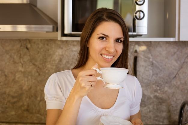 Giovane bella donna in cucina seduta al tavolo con una tazza in mano sorridendo
