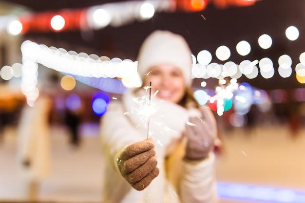 Giovane bella donna in berretto lavorato a maglia e sciarpa in piedi in città con sparkler luce bengala