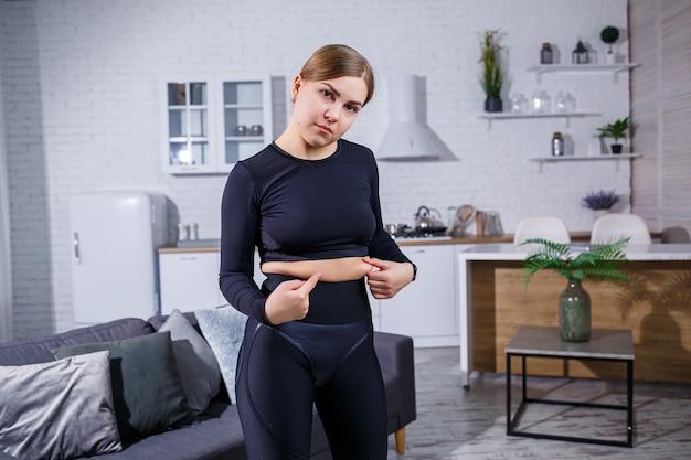 La giovane bella donna in leggings e un top mostra una piega sulla pancia. uno stile di vita sano. la donna fa sport a casa. combattere l'eccesso di peso a casa