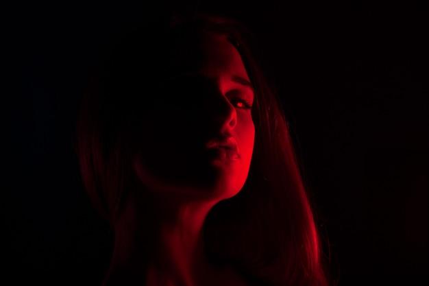 Giovane bella donna in biancheria che posa alla luce posteriore rossa