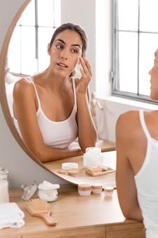 Giovane bella donna che esamina lo specchio