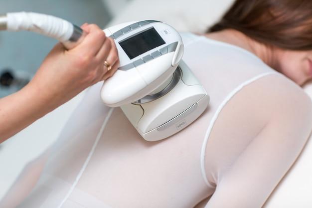 La giovane bella donna e il gpl massaggiano la procedura posteriore nella clinica della stazione termale. processo dell'apparato gpl con massaggio linfatico drenaggio.