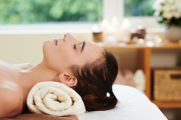 Giovane bella donna sdraiata con gli occhi chiusi e rilassante nella spa