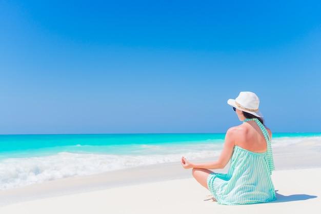 Giovane bella donna in una meditazione sulla spiaggia