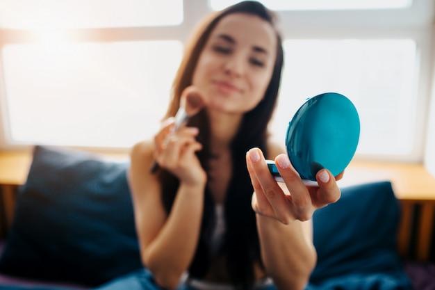 Giovane bella donna nel letto di mattina a casa. brunette attraente sorridente che usando spazzola e polvere con lo specchio. trucco con gioia. tempo di camera da letto.