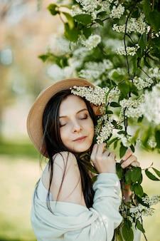 Giovane bella donna vicino ai fiori di ciliegio degli uccelli. ciliegio di uccello fiorito e donna felice in un cappello.